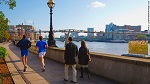 Two men run past a couple strolling by the River Thames