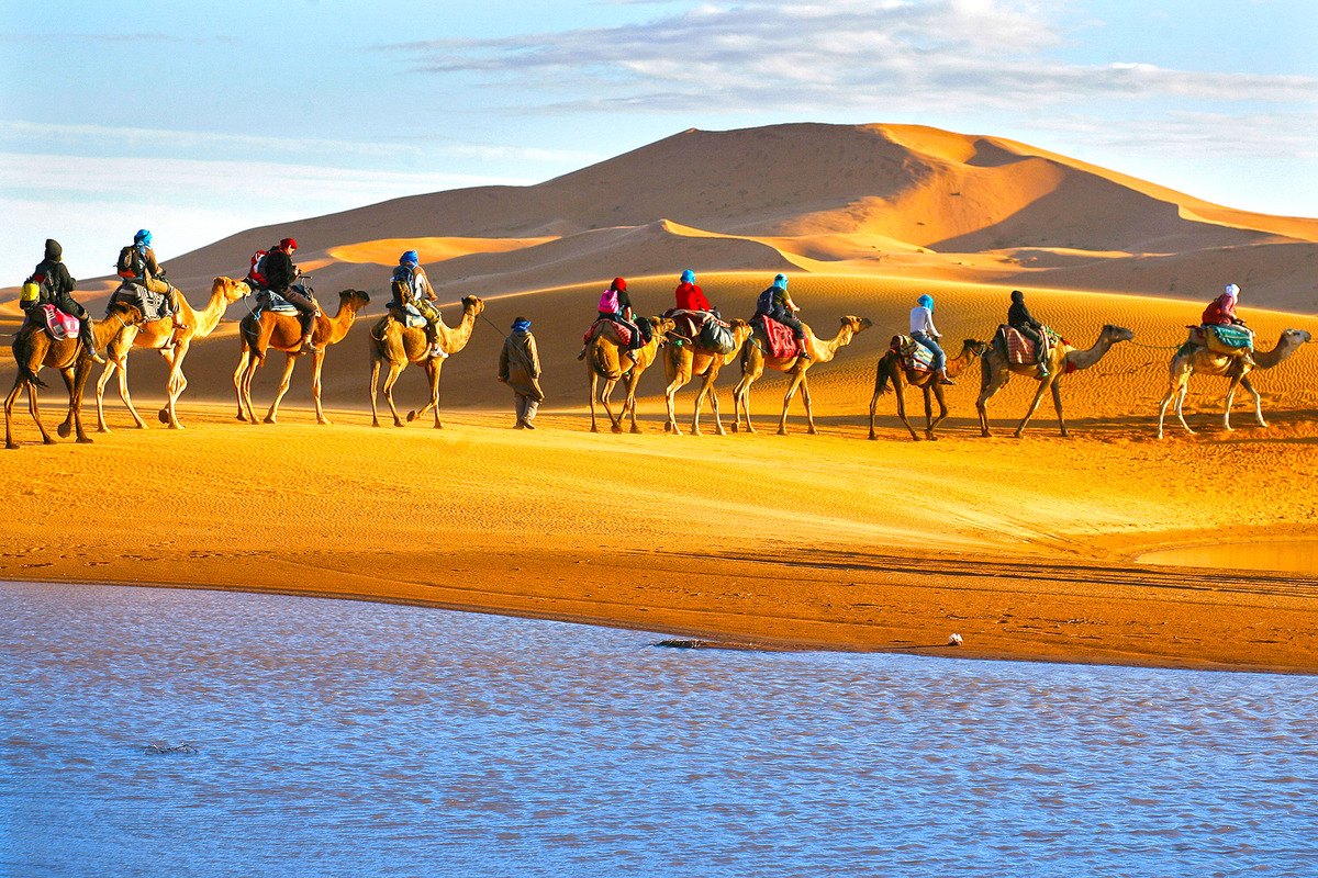 Caravan of tourists passing the desert on camels with lake in foreground